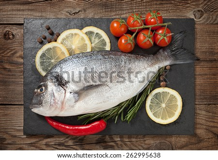 Fresh fish, lemon, spices and cherry tomatoes on a stone board - stock photo