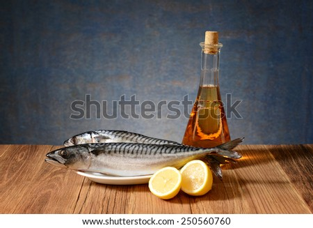 Fresh fish mackerel, lemon and wine in the bottle on the table - stock photo