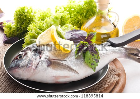 Fresh fish of dorado on a frying pan with a lemon and olive oil - stock photo
