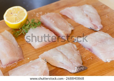 fresh fish on wooden cutting board ready for cooking - stock photo