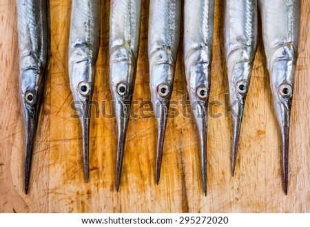 Fresh fish on wooden kitchen board - stock photo