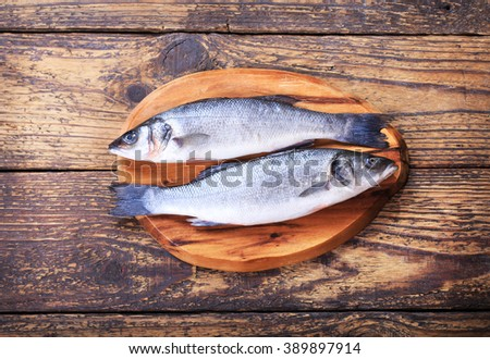 fresh fish sea bass on wooden table - stock photo