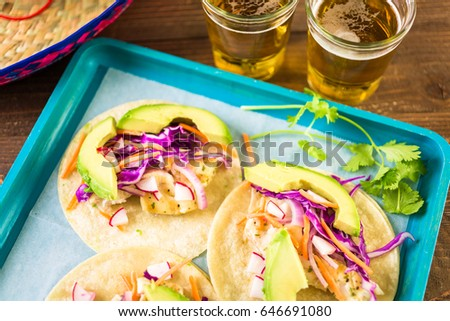 Fresh fish tacos with cod and purple cabbage on a white corn tortillas.