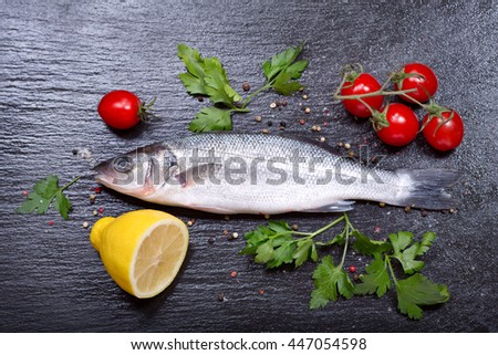 fresh fish with herbs and vegetables on dark background