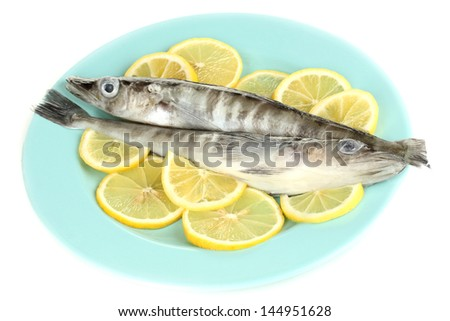 Fresh fish with lemon on plate isolated on white