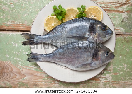 Fresh fishes (Sparus aurata) with lemon and parsley on a plate served on rustic green table - stock photo