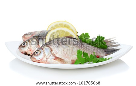 Fresh fishes with lemon and parsley on plate isolated on white - stock photo