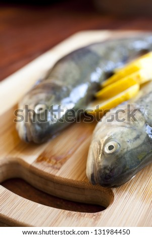 Fresh fishes with lemon on wooden cutting board - stock photo