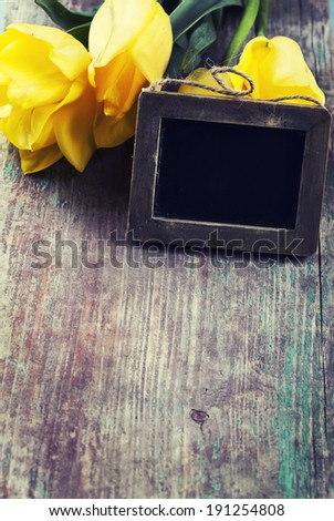 Fresh flowers and empty blackboard with place for text on aged wooden background. - stock photo