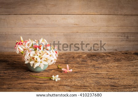 Fresh flowers in a vase on old wood still life - stock photo