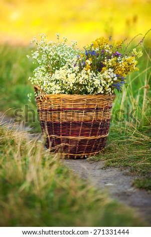 fresh flowers in handmade basket in spring meadow. bunch of flowers. many field flowers.   - stock photo