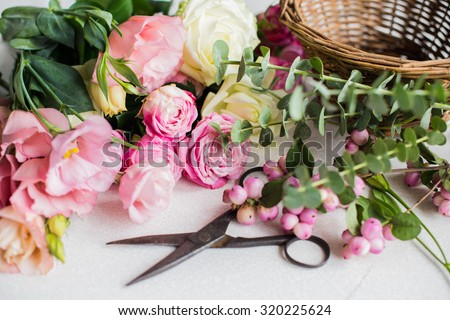 Fresh flowers, leaves, and tools to create a bouquet on a table, florist's workplace. - stock photo