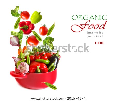 Fresh flying vegetables in a red casserole on a white background. - stock photo