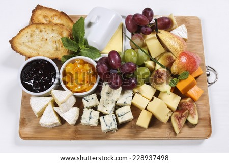 Fresh food arrangement of different types of cheese and fruits, served with bread and butter on a wooden board, menu background