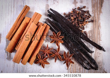 Fresh fragrant cinnamon sticks, vanilla pods, star anise and cloves on old rustic wooden surface plank, seasoning for cooking or baking - stock photo