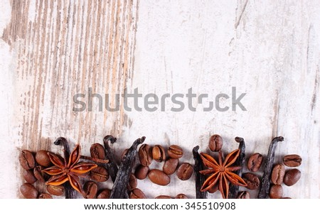 Fresh fragrant vanilla sticks pods, star anise and coffee grains on old rustic wooden surface plank, copy space for text, seasoning ingredients for cooking or baking - stock photo