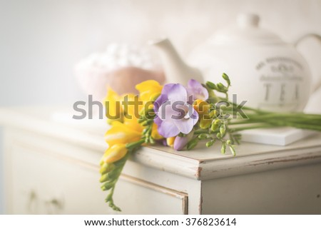 fresh freesias on the top of bedside cabinet - stock photo