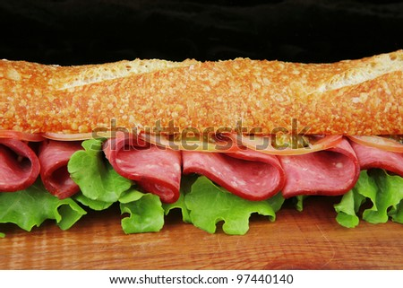 fresh french baguette with chicken smoked sausage on wood over black - stock photo