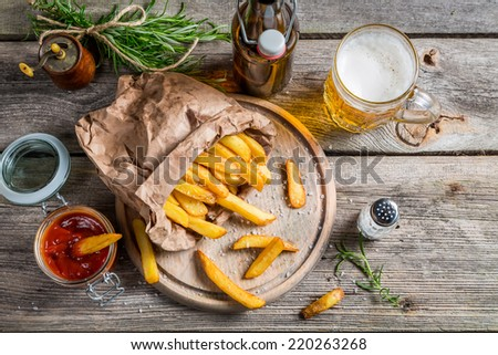 Fresh french fries served with beer - stock photo