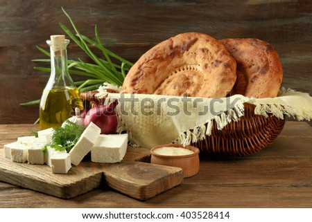 Fresh fried bread and other products on wooden background