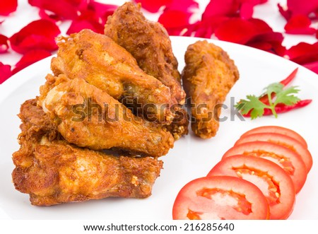 Fresh fried chicken on a white plate set on table.