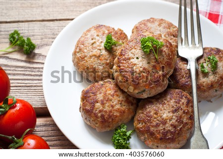 Fresh fried cutlets in a white plate on wooden table.