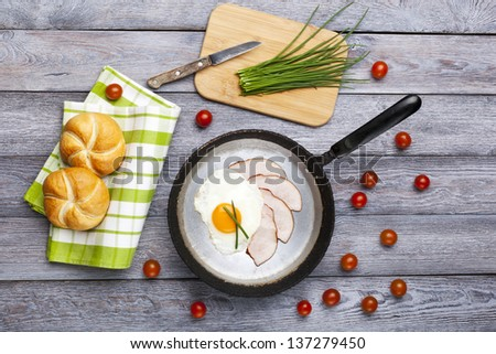 Fresh fried egg and pork ham served on pan with rolls, tomatoes and chives. English breakfast.