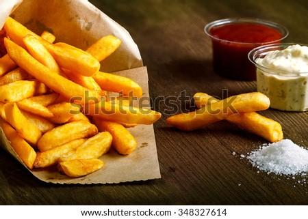 Fresh fried french fries with ketchup and white sauce on wooden background - stock photo