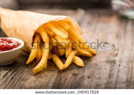 Fresh fried french fries with ketchup on wooden background - stock photo