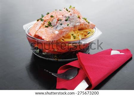 fresh fried natural pink salmon on italian traditional tagliatelle backed with tomato and vegetables served over black wooden table - stock photo