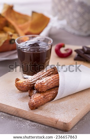 fresh fried pumpkin churros with chocolate on cutting board. Vertical image.