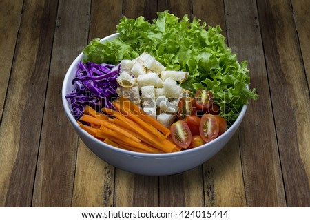 Fresh from the farm Used to make salad. Put in a bowl placed on an old wooden table. The food consists of fresh vegetables. Served with creamy dressing. - stock photo