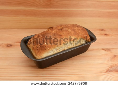 Fresh from the oven - a loaf of oat and linseed bread in the tin - stock photo