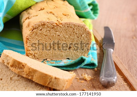 Fresh from the oven gluten free bread on a cutting board - stock photo