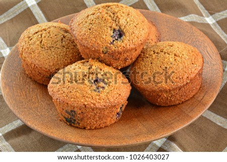 Fresh from the oven homemade blueberry bran muffins on rustic wooden plate in horizontal format and shot in natural light