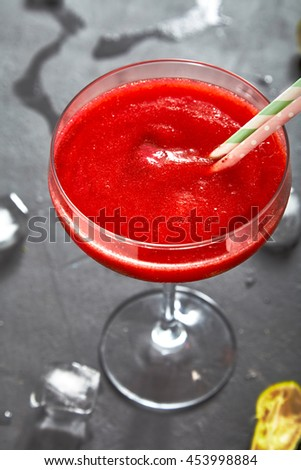 Fresh frozen pureed strawberry margarita in margarita glass with two cocktail tubes in it, ice and limes near glass. Dark stone background. - stock photo