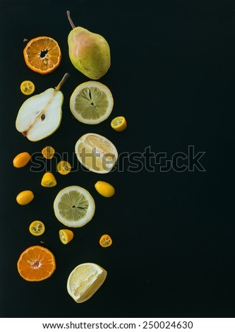 Fresh fruit and citrus mix on black: pieces of pear, mandarin; grapefruit, lemon a kumquat over a black backdrop with a copy space. Top view - stock photo