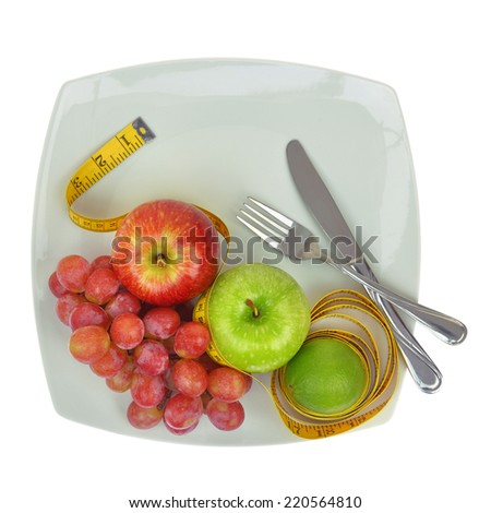Fresh fruit and measuring tape on a plate
