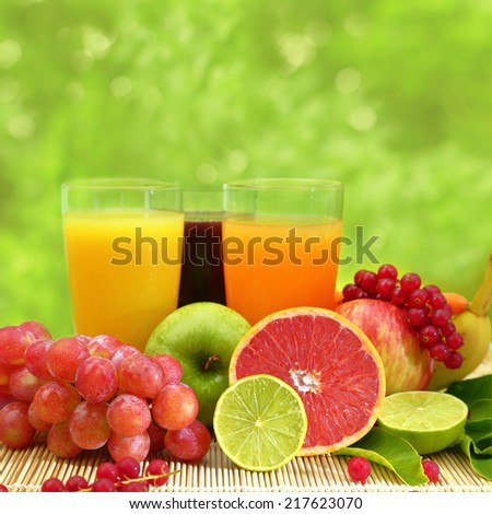 Fresh fruit and three glasses full of juice - stock photo