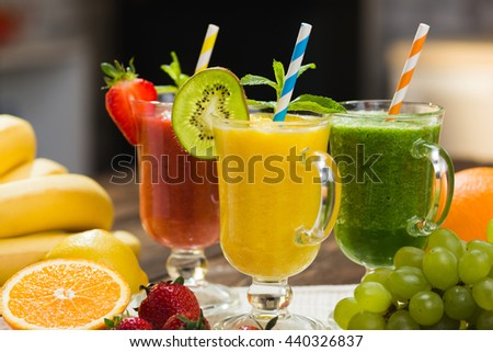 Fresh fruit and vegetable smoothie on kitchen table in glass