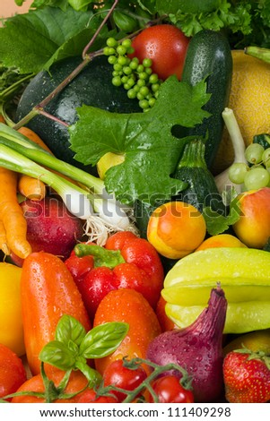 Fresh fruit and vegetables like tomatoes, zucchini, melons, grapes and leaves wet arranged in a group, natural still life for healthy food - stock photo