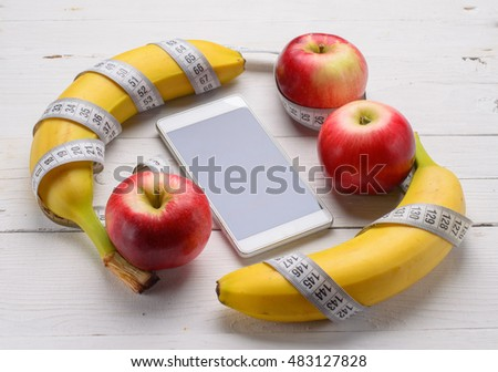 Fresh fruit: bananas and apples on a wooden table.Measuring tape and a mobile phone, sports nutrition.