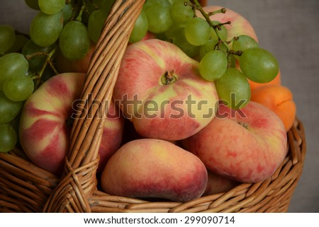Fresh fruit basket from summer garden with green grapes and pink peaches and orange apricot - stock photo