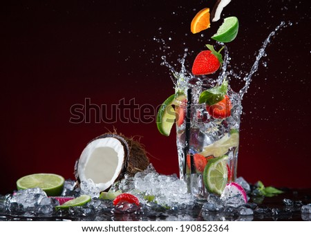 Fresh fruit cocktail in freeze motion splashing, close-up. - stock photo