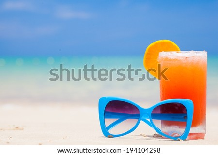 fresh fruit cocktail with blue sunglasses on tropical beach - stock photo