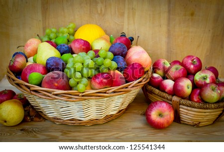 Fresh fruit in the basket on the wooden table - stock photo