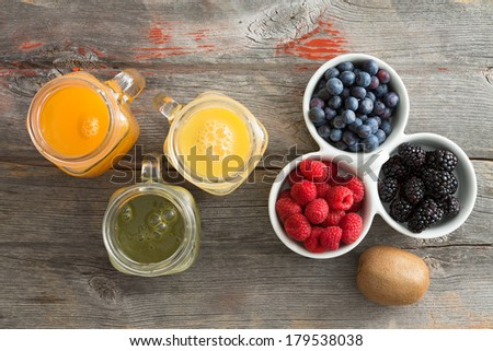 Fresh fruit juice in three glass jugs with mango, orange and kiwifruit blend served on an old rustic wooden table with a dish of raspberries, blueberries and blackberries for healthy picnic snacks - stock photo