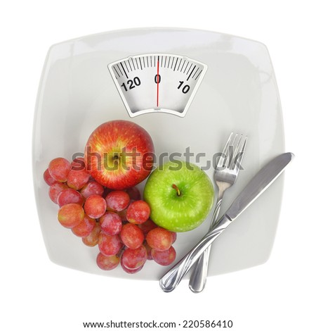 Fresh fruit on a plate with weighing scale - stock photo