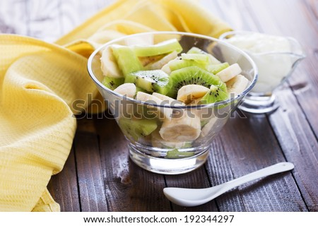 Fresh fruit salad in bowl on wooden background. Selective focus, horizontal.