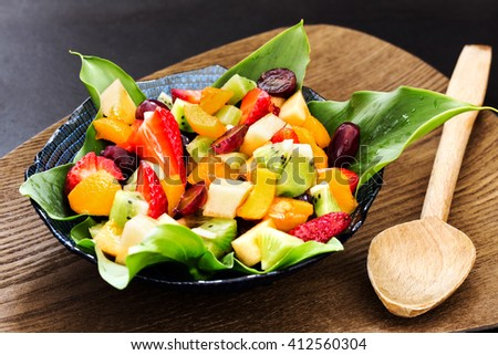 fresh fruit salad inside bowl with decorative calla leaves over wooden support